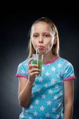 Little girl drinking juice, studio shot — Stock Photo