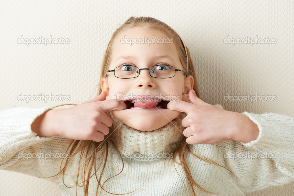 Funny portrait of a little girl in eyeglasses with tongue out — Stock Photo #5248315