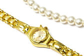 Golden wrist watch and pearl necklace — Stock Photo