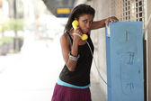 Woman talking on a pay phone — Stock Photo