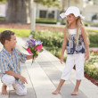 Boy giving flowers to the girl - Foto Stock