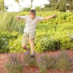 Boy jumping over a bush — Stock Photo #4149357