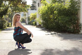 Woman squatting in fashionable clothing — Stock Photo