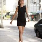 Woman walking in a black dress — Stock Photo