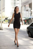 Woman walking in a black dress — Stock Photo