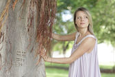 Woman posing by a tree — Stock Photo