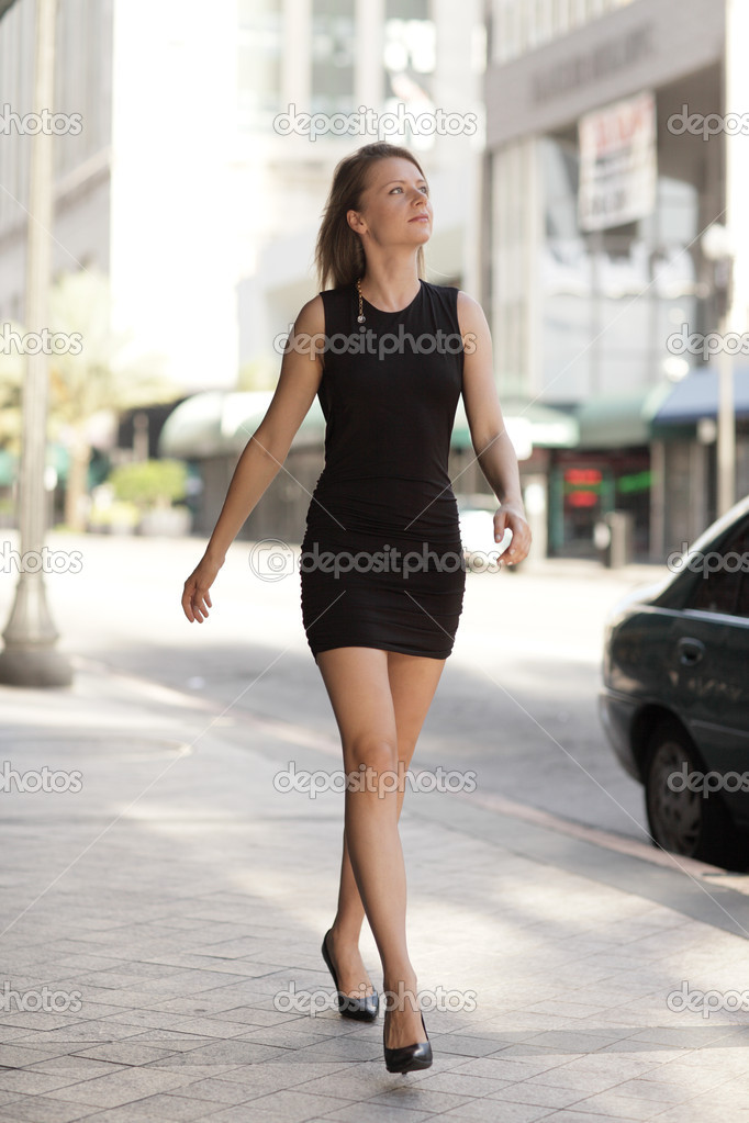 Attractive woman in a black dress walking in the city — Stock Photo #4216014