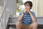 Boy sitting on a staircase — Stock Photo