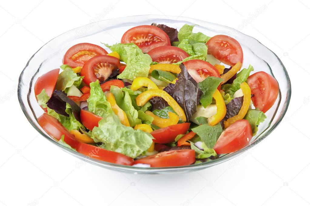 A glass bowl full of a variety of vegetables in a colorful tossed salad. — Photo #3965073