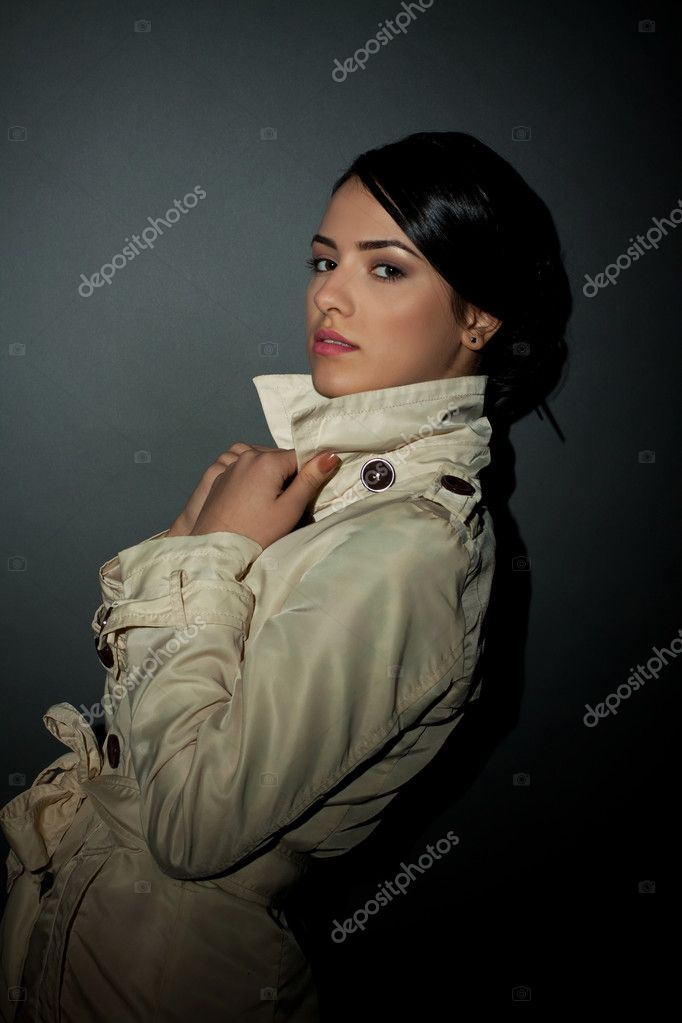Slim young fashion model wearing a trench coat and pulling its collar — Stock Photo #5122568
