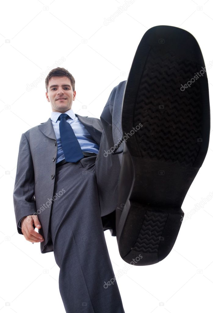 Picture of a smiling business man steping on something, over white — Stok fotoğraf #5122750