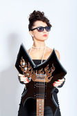 Fashion woman with sunglasses holding a electric guitar — Stock Photo