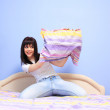 Woman having pillow fight - Stock Photo