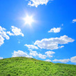 Stock Photo: Green grass hills under midday sun
