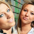Young women with a brick wall — Stock Photo