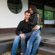 Young couple on the steps of a house — Stock Photo