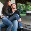 Young couple on the steps of a house — Foto de Stock