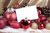Christmas decorations with blank card over white background — Stock Photo