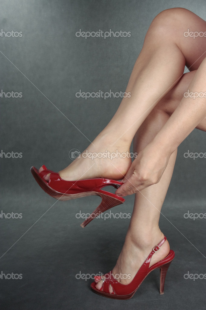 Beautiful woman legs putting on red shoes  over grey — Stock Photo #4350006