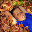 Preteen boy laying in autumn leaves — Stock Photo