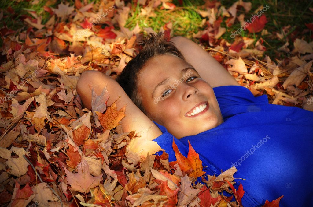 Preteen boy laying in a pile of fallen autumn leaves in the shade.  The boy is smiling and looking at the camera.  — Stock Photo #5243498