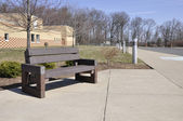 Empty bench by a school — Stock Photo
