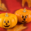 Mini Pumpkins with Funny Faces on a Red Autumn Cloth Background - Stock Photo