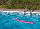 Azul piscina. escada e brinquedo piscina rosa em plena luz solar — Fotografia Stock