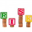 Stock Photo: Alphabet blocks spelling RISK on stacks on pennies