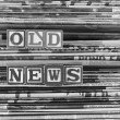 "Stock Photo: Old newspapers stacked and ""Old News"" is written in Block Letters"