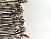 Old newspapers stacked from the top to bottom of the frame isolated on whit — Stock Photo