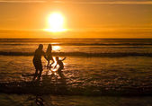 Silhouettes of children playing on the beach against the sunset — Stock Photo