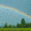 A rainbow is capture through a rain spotted windshield with the focus on th — Stock Photo