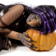 Girl dressed up as a witch leaning on a pumpkin — Stock Photo