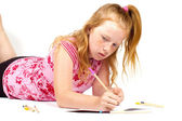 Redhead girl is doing her homework — Stock Photo