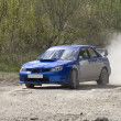 Blue racing rally car on gravel road — Stock Photo #5210478