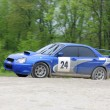 Blue racing rally car on wet gravel road — ストック写真