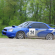 Blue racing rally car on wet gravel road — Stock Photo #5210499