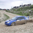 Blue racing rally car on wet gravel road — Stock Photo #5210508