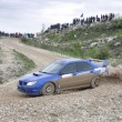 Stock Photo: Blue racing rally car on wet gravel road