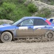 Blue racing rally car on wet gravel road - Stock Photo