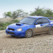 Blue racing rally car on wet gravel road — Stock Photo