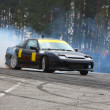Stockfoto: Black racing car drifting on road