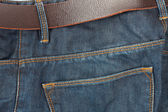 Blue jeans with old brown belt — Stock Photo