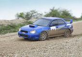 Blue racing rally car on wet gravel road — Stockfoto