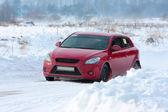 Red rally car on winter racing track — Stockfoto