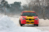 Rally red and yellow car on snow track — Stock Photo