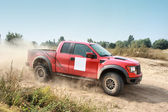 Power red off-road car on dirt road — Stockfoto