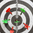 Six red and green darts on game board — Lizenzfreies Foto