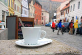 Old city street, house with windows and cup of coffe — Stockfoto